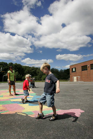 Essex: Charlie Roy, 5, steps on his home state of Massachusetts while looking for the states he knows with his brother Alex, 3, and mother Deidre behind the Essex Elementary School Friday afternoon.  The boys soon ran to the Eagle's Nest Playground for a game of hide and seek. Mary Muckenhoupt/Gloucester Daily Times