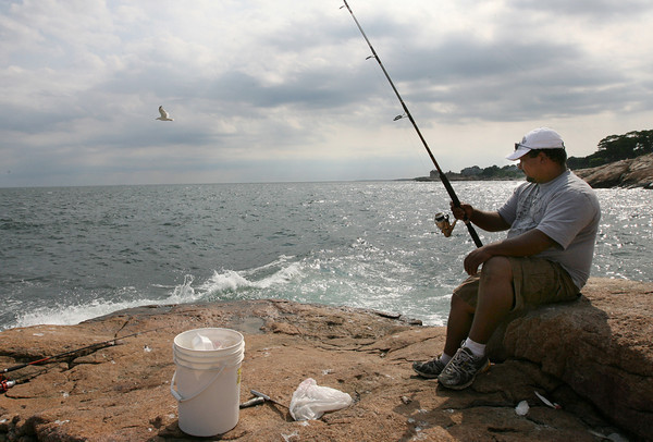 Gloucester: Nells Olivera of Peabody waits for the fish to bite off Rafes Chasm in Magnolia yesterday afternoon. Olivera says he comes to the area once or twice a month to fish. Photo by Kate Glass/Gloucester Daily Times