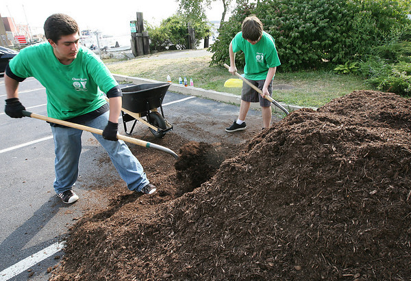 Gloucester: Dominic Tocco and Steven Verga of the YMCA Clean Team load mulch into a wheelbarrow as they work at Gordon Thomas Park near the Jodrey State Fiesh Pier yesterday afternoon. The Clean Team, which employs 150 local teens, has been maintaining many of Gloucester's public parks as well as Main Street throughout the summer. Photo by Kate Glass/Gloucester Daily Times