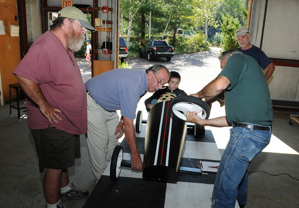 Gloucester: Dan Conrad President of the Fish Box Durby and Bob Ryan Treasurer (left) look on as Greg Bover inspects the wheel on Robbie Pata 11, Fish Box that he and his great uncle Al Viator built together, Sunday morning at C.B Fisk Industrial Park. All cars and drivers have to be registerd,weighed and inspected on that date. Desi Smith/Gloucester Daily Times. August 29,2010.