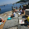 Rockport: Students in the Rockport Art Association water color class, including Zak Poretta, 9, right, sit at the end of T-wharf and do their best to paint a harbor scene including Motif No. 1 Thursday morning.  Becky Merry who teaches the one week art classes was happy to have a less humid day to take the kids outside to paint. Mary Muckenhoupt/Gloucester Daily Times