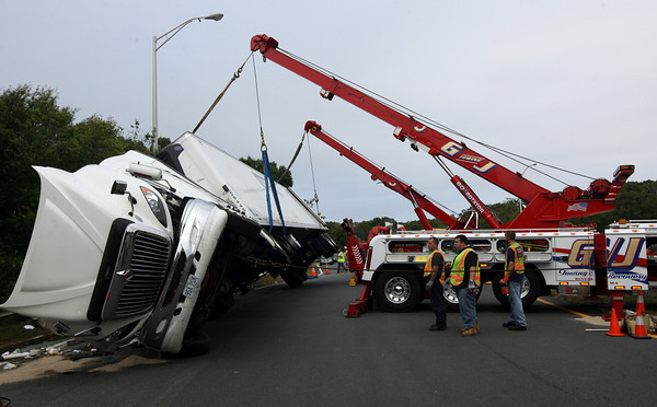 Gloucester: Tow trucks from Tally's and G/J Towing lift a tractor trailer that rolled over at Blackburn Circle yesterday afternoon, closing Route 128 southbound for over 4 hours. The driver was not seriously injured in the crash. Photo by Kate Glass