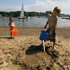 Manchester: Aisling Twombly, 3, carries a bucket of water to help her brother, Brennan Twombly, 5, build a pool in the sand at Tuck's Point on Tuesday afternoon. Photo by Kate Glass/Gloucester Daily Times