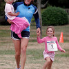Gloucester: Nan Gorton Demaso carries Libby Lawler as she runs with her daughter, Annie Grace Demaso during the kids run at Stage Fort Park following Run Gloucester! yesterday morning. Photo by Kate Glass/Gloucester Daily Times