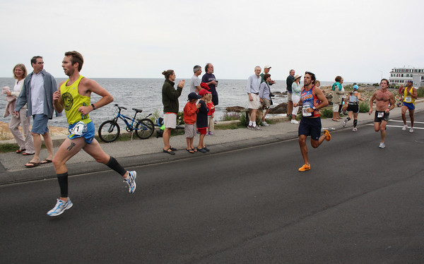 Gloucester: Spectators along the back shore cheer on runners in the first Run Gloucester! 7-mile road race yesterday morning. Running are Wesley Lassen of Beverly, Chris Johnson of Wellesley, and Matt Curran of Gloucester, and Tony Darocha of Roxbury. Photo by Jeff Pope/Gloucester Daily Times