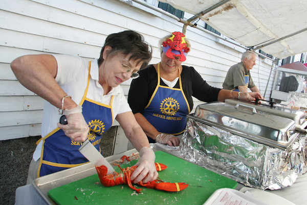 Rockport: Carol Linsky tries her hand at cracking lobsters with Ruth George at the Rotary Club's Lobsterfest in front of the American Legion Hall  Saturday afternoon. Linsky had trouble cracking the claws on this particular lobster and had to give the job over to George.  The Rotary expected to sell over 600 lobsters this year with proceeds from the event benefiting local community service projects and the Rotary Club's scholarship fund. Photo by Mary Muckenhoupt/Gloucester Daily