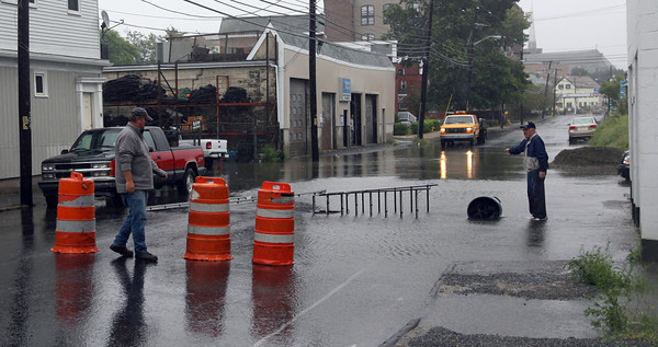 Gloucester: A Gloucester DPW employee places barrels in front of a flooded section of Maplewood Ave. yesterday. Photo by Kate Glass/Gloucester Daily Times