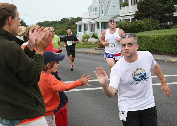 One runners gives the  youngsters watching the race on the Back Shore a high five Sunday morning. Photo by Jeff Pope/Gloucester Daily Times