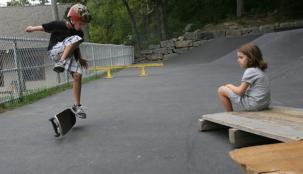 Rockport: Gabrielle Accardi, 6, watches her brother, Anthony Accardi, 9, practice tricks at the Matt Waddell Memorial Skateboard Park yesterday afternoon. The park recently received an upgrade of a new fence and new stairs leading up to the park. Photo by Kate Glass/Gloucester Daily Times