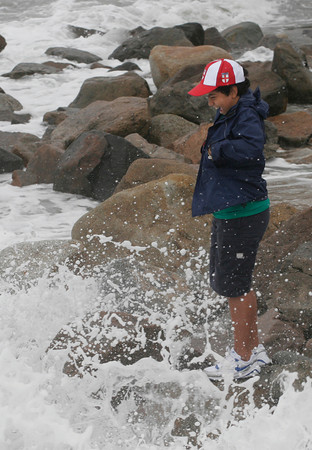 Rockport: Sam Glass, 11, of New York laughs as he gets splashed by a wave at Cape Hedge Beach yesterday morning. Many people stopped to check out the surf. Photo by Kate Glass/Gloucester Daily Times