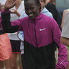 Gloucester: Lineth Chepkarui of Kenya waves to the crowd as she walks to receive her award for being the first woman to cross the finish line of the first Run Gloucester! 7-mile road race yesterday morning. Photo by Kate Glass/Gloucester Daily Times