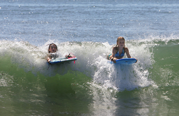 Rockport: Abigail Reese, 12, and Morgan Browning, 12, catches a wave on their boogie boards at Cape Hedge Beach Thursday monring. The surf was high and churning up a lot of seaweed after the past few days of stormy weather. Mary Muckenhoupt/Gloucester Daily Times