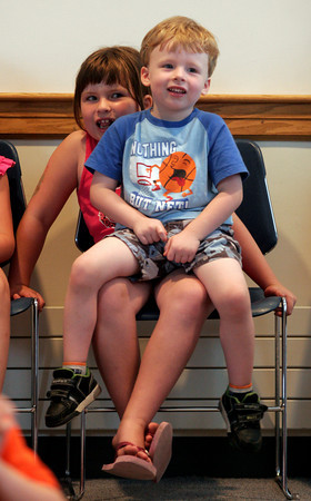 """Rockport: Austin Story, 3, sits in the lap of his sister, Caitlyn Story, 6, as they listen to stories during """"Where the Green Things Are"""" at the Rockport Public Library on Wednesday afternoon. Photo by Kate Glass/Gloucester Daily Times"""