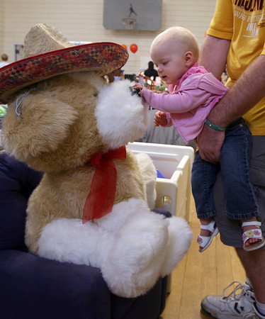 Gloucester: Taylor Peek, 1, gets a lift from her father, Rick Peek, so she can check out a giant stuffed animal at the Magnolia Library on Sunday during Magnolia's Giant Sidewalk Bazaar and Roadshow. Photo by Kate Glass/Gloucester Daily Times