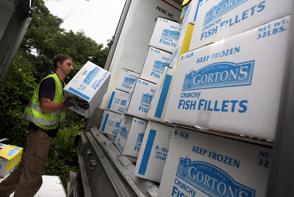 Gloucester: Dan Neal of Tally's Towing Service unloads boxes of Gorton's Fish Fillets from a rolled over tractor trailer into another trailer at Blackburn Circle so they can upright the vehicle. Photo by Kate Glass
