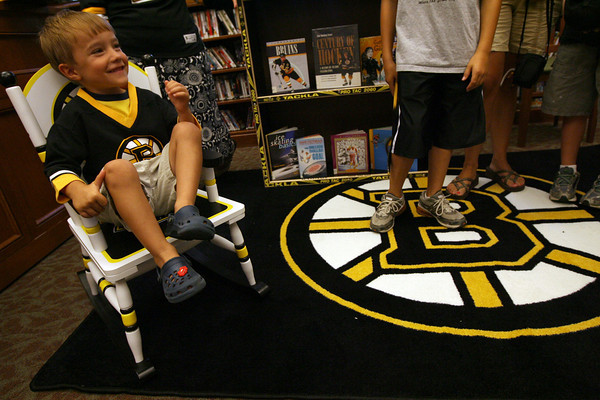 "Manchester: Cole Edmonds, 5, sits in a rocking chair that was donated to the Manchester Public Library by the Boston Bruins yesterday afternoon. In addition to the rocking chair, the library received a rug, a bookcase made out of hockey sticks, two copies of ""Casey and Derrek on the Ice,"" a visit from the mascot, Blades, and goodie bags. Photo by Kate Glass/Gloucester Daily Times"