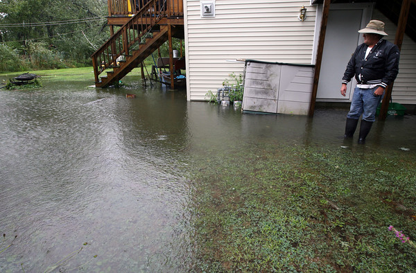Gloucester: Ron Johnson looks out over his sister's flooded yard on Myrtle Court yesterday morning. Johnson says the yard and basement flood everytime there is a heavy rain because there is no curb to prevent water flowing from Maplewood Ave. into the yard. Photo by Kate Glass/Gloucester Daily Times