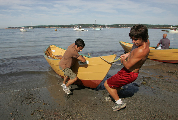 Gloucester: L.J. Robertson, right, and Randy Parisi pull their boat up onto Niles Beach after rowing in the International Dory Race Elimination races Saturday morning. Mary Muckenhoupt/Gloucester Daily Times