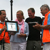 Gloucester: Dave McGillivray presents Mayor Carolyn Kirk with the #1 bib as Gloucester Fishermen Athletic Association co-presidents Dick Wilson and Jonathan Pope look on before the start of the first Run-Gloucester 7-mile road race yesterday morning. Money raised by the race will benefit the GFAA, which hopes to assist local athletes in paying user fees to play sports at Gloucester High as well as renovate Newell Statium. Photo by Kate Glass/Gloucester Daily Times