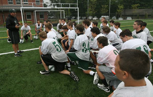 Manchester: Manchester Essex football coach Mike Athanas speaks with his players during practice at Hyland Field yesterday afternoon. Photo by Kate Glass/Gloucester Daily Times