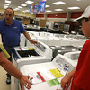 Ed Muzio discusses the benefits of different types of washers and dryers as Julie Ryan and her son, Stephen, shop at Sears in advance of the tax free weekend, which is this weekend. Photo by Kate Glass/Gloucester Daily Times