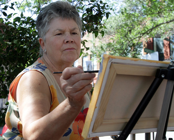 David Le/Gloucester Daily Times. Bonnie Slyvester, of Gloucester paints in the shade along Main St. on Monday afternoon. 8/23/11.