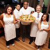 David Le/Gloucester Daily Times. Mauricio Souza, center, owner of Valentino's Pizza, is surrounded by from left, Emily Avila, Paulo Vitor, former owner, Carlo Barbara, and Alessandra Russo. Valentino's was closed for over 6 months and recently reopened for business. 8/22/11.