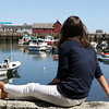 David Le/Gloucester Daily Times. Sarah Brink, from New York, sits and relaxes on a wall overlooking Rockport Harbor on Thursday afternoon. 8/25/11.