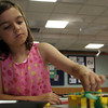 Annika Vanderberg, 9, of Gloucester starts construction on her yellow Lego house during a meeting of the Lego Club at the Gloucester Lyceum and Sawyers Free Library. Photo by Maria Uminski/Gloucester Daily Times