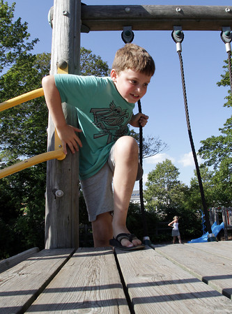 David Le/Gloucester Daily Times. Emerson Kahle, 8, of Manchester, climbs up the playground ropes at Masconomo Park in Manchester on a warm August afternoon. 8/26/11.