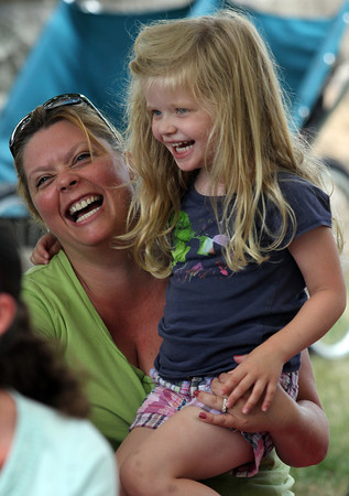"Monica Grant and her daughter, Clara, laugh as singer-songwriter Tom Sieling changes Clara's name to ""Wara"" for a song during ""Bugs, Baboons & Tunes"" at the Manchester Library yesterday afternoon. Photo by Kate Glass/Gloucester Daily Times"
