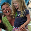 """Monica Grant and her daughter, Clara, laugh as singer-songwriter Tom Sieling changes Clara's name to """"Wara"""" for a song during """"Bugs, Baboons & Tunes"""" at the Manchester Library yesterday afternoon. Photo by Kate Glass/Gloucester Daily Times"""