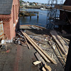 David Le/Gloucester Daily Times. A look out at the water and the roofing renovations that are taking place at the old paint factory from the second floor of the old building. 8/17/11.