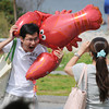 Rockport: Dahyuu Lu plays around with a lobster ballon as Weilan Yeh takes his picture at Lobster Fest Saturday afternoon. The pair from Taiwan are staying in the Boston Area.  Desi Smith/Gloucester Daily Times. August 13, 2011