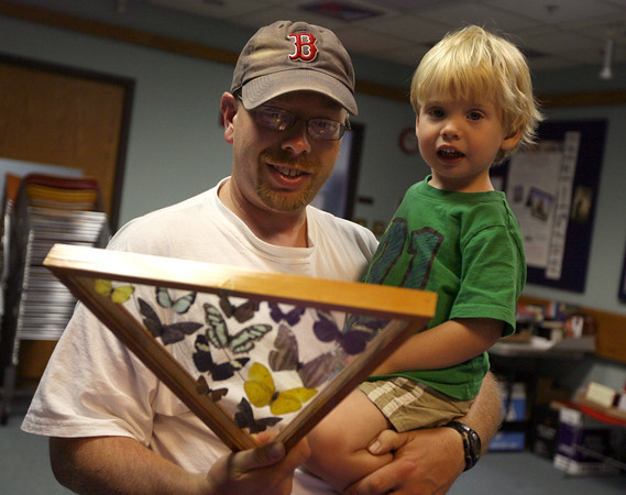 "Jeff Morin and his son, Nathan, 2, check out a display of butterflies at the Sawyer Free Library yesterday morning during the program, ""Butterflies with Kim Smith."" Photo by Kate Glass/Gloucester Daily Times"