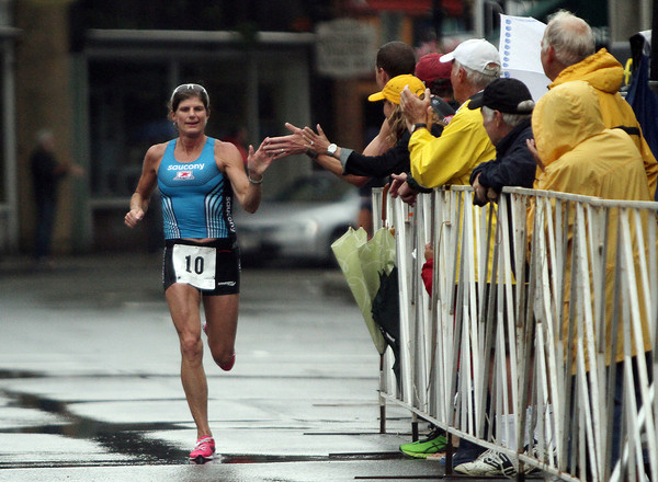 David Le/Gloucester Daily Times. Last year's triathlon winner Karen Smyers high fives spectators as she runs down a rain-soaked Main St. towards the finish line on Sunday morning. 8/7/11.