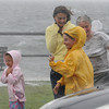 Gloucester: People brave the high winds and rain to have their photo taken,or watch the large waves crashing onto the boulevard during high tide Sunday afternoon.  Desi Smith /Gloucester Daily Times. August 28,2011