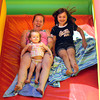 Gloucester: Jessica Ireland holds her daughter, Jade, 19 months, as she goes down a slide with Haley Ireland, 6, at the Sidewalk Bazaar on Main Street in Gloucester yesterday. The slide was set up by Prime Time Party Zone. Photo by Kate Glass/Gloucester Daily Times
