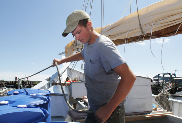 David Le/Gloucester Daily Times. Zach Teal, 16, of Essex, works to tightly fasten a rope railing to the side of the Schooner Ardelle on Monday afternoon in preparation for its journey to Maritime Gloucester on Wednesday evening.  8/22/11.
