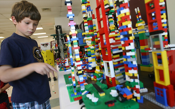 Peter Tingley points out the towers he's made from Legos during the Rockport Summer Fun program. Tingley made one tower similar to the Empire State Building and also helped rebuild an airplane out of Legos. Photo by Kate Glass/Gloucester Daily Times