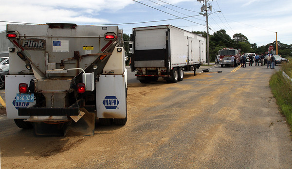 David Le/Gloucester Daily Times. A truck full of sand stops behind the trailer of an 18-wheeler which had leaked fuel all along Causeway St. on Wednesday morning. Crews worked to clean up the spill well into Wednesday afternoon. 8/24/11.