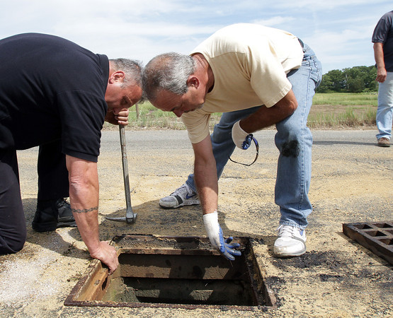 David Le/Gloucester Daily Times. Jay Prince, left, of the Gloucester Fire Department, and Tony Puglisi, of Gloucester DPW peer into an open drain to see if fuel from a leaking tractor trailer had polluted the marsh. The truck had leaked gas all along Causeway St. forcing it to be shut down for most of Wednesday while cleanup took place. 8/24/11.