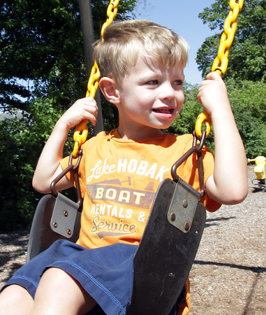 David Le/Gloucester Daily Times. Carson Croft, 4, of Manchester, smiles at his twin brother Jarrett (not pictured),while sitting on a swing at Masconomo Park on an August afternoon. 8/23/11.