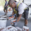David Le/Gloucester Daily Times. Gloucester DPW mason Scott Amero, piles bricks from one of town hall's chimneys after he and Joe Silva, back left, removed them on Friday afternoon. The chimneys were condemned and were eventually going to be taken down, but with the impending hurricane, an order was given to have them taken down immediately. 8/26/11.