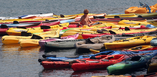 Danny Mears of North Shore Outdoors Kayak Center wrangles some of the kayaks in the harbor during his shift at the center. Photo by Maria Uminski/Gloucester Daily Times