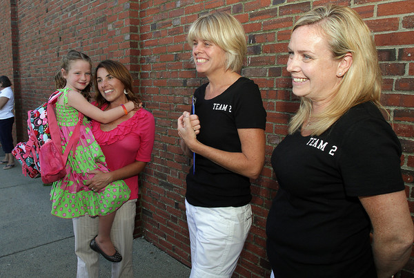 Kassey Heaney, 7, left and her mother Laurie, chat with 2nd grade teachers Jen Dahlgren, center, and Julie Raftelis, right after the first day of school on Tuesday afternoon.. David Le/Gloucester Daily Times