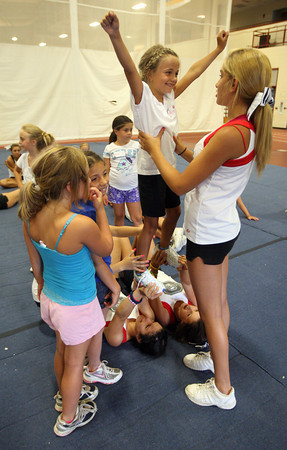Gloucester: Avery Smith smiles at Gloucester High School cheerleader Marina Tarantino as she is held up by Jesenia Martinez and Veronica Gibbs during GHS Cheerleaders Mini Camp at the Benjamin A. Smith Fieldhouse yesterday. The camp, which is for kids age 5-11, runs through Thursday. Photo by Kate Glass/Gloucester Daily Times