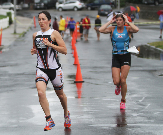 David Le/Gloucester Daily Times. Catherine Sterling, left, is shadowed closely by Karen Smyers, right as they begin the running portion of the Gloucester Fisherman Triathlon on Sunday morning. Sterling was the eventual winner while Smyers took 3rd in the women's elite race. 8/7/11.