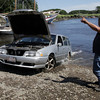 David Le/Gloucester Daily Times. Scott Sholds, of Tally's Truck Center Towing Company instructs driver Kevin Hunt as he pulls a flooded Volvo station wagon out of the Essex River on Monday afternoon after the car rolled in while trying to launch a boat. 8/22/11.