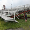 Craig Saundrs and Kyle Lucido trim the grass around the bleachers at Newell Stadium yesterday. The city is seeking proposals for naming rights to the field with the minimum bid starting at $500,000. Photo by Kate Glass/Gloucester Daily Times